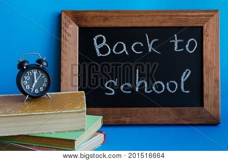 Back to school concept. School supplies on blue background. Frase Back to school written on blackboard with old books and clock.