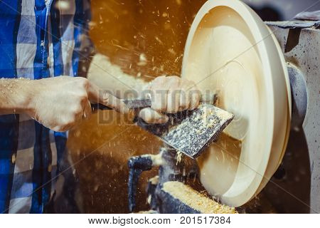 man turning a wooden plate on a lathe