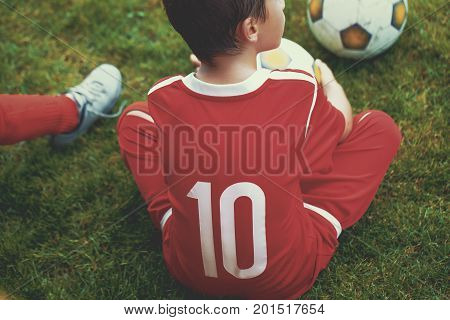 Little soccer forward player boy sitting on field training
