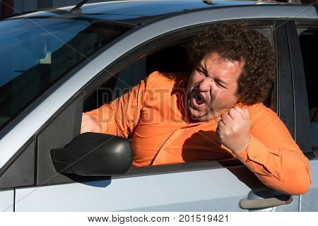 Funny man in the car. Street. Heat. A fat guy in a blue car.