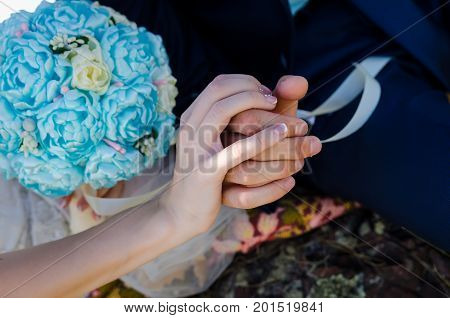 Hands of Engaged Couple - Love and Commitment Concept with wedding bouquet