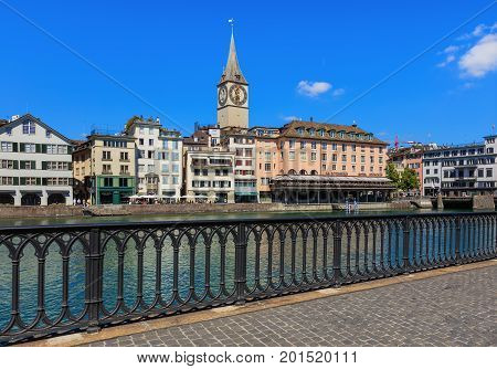 Zurich, Switzerland - 18 June, 2017: city's old town buildings along the Limmat river, clock tower of the St. Peter Church, Hotel Storchen. Zurich is the largest city in Switzerland and the capital of the Swiss canton of Zurich.