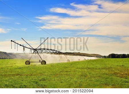 Modern agricultural irrigation system watering a farm field on sunny summer day. Central pivot sprinkler system Automated mobile irrigation sprinklers system with wheels on cultivated agricultural field.