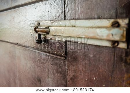 A latch of bar lock at the old wooden door. Protect Anti-theft Protection.