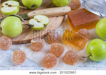 Sweet natural dessert. Apple marmalade and fresh green apples on an old wooden table.