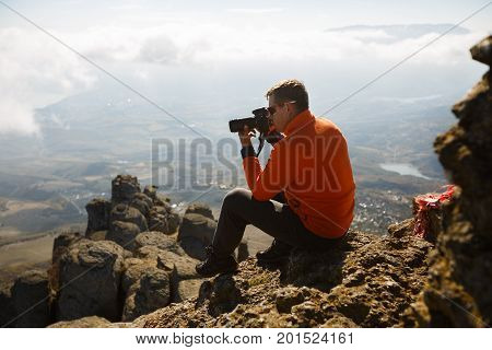 Young professional traveller man with dslr camera shooting outdoor fantastic mountain landscape. Hiker sits on a rock at the high summit above clouds
