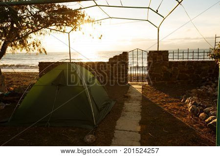 Tent on backyard near the beach with sea on background in the morning sunrise