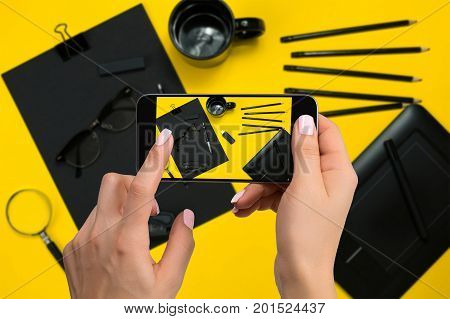 Shooting black stationery on phone's camera. Stationery on yellow background. Close-up woman's hand holding phone.