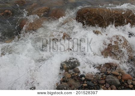Waves of Lake Superior splash on rocks at Pictured Rocks National Lakeshore, Upper Peninsula of Michigan