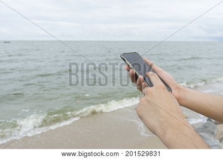 A man using left index finger for texting cellphone on the beach