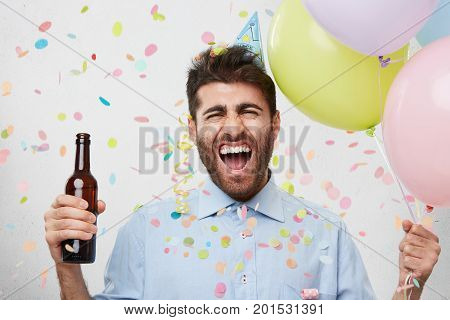 Waist Up Portrait Of Happy Well Dressed Bearded Man Holding Bottle With Drink And Colorful Balloons,
