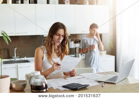 Puzzled Female Accounter Trying To Understand What Is Written In Paper, Reading It With Frustrated L