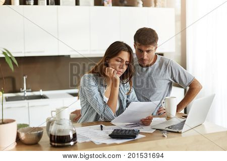 Picture Of Young Wife And Husband In Kitchen Having Concentrated Looks While Reading Notification Fr