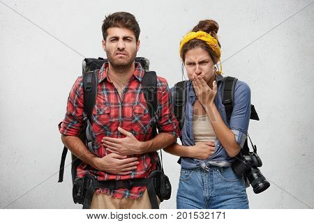 Food Poisoning, Nausea And Sickness Concept. Portrait Of Young Man And Woman Tourists Feeling Stomac
