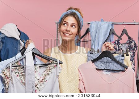 Woman Shopaholic Being In Boutique Choosing Many Outfits, Looking With Dreamy Expression Up, Not Kno