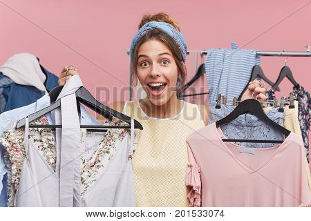 Glad Female Holding Hangers With Clothes, Feeling Joy To Do Shopping In Department Store. Happy Fema
