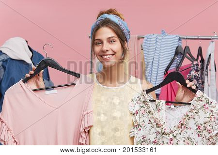 Cheerful Female Wearing Scarf On Head And Shirt, Smiling Pleasantly While Holding Hangers With Two D