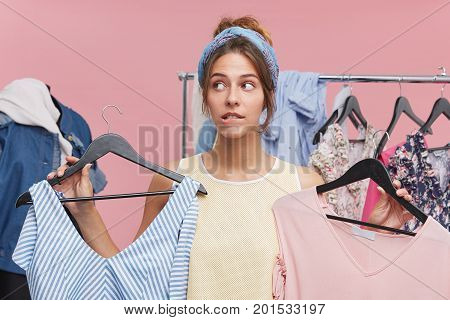 Cute Female Purchaser Standing In Fitting Room, Holding Two Stylish Dresses, Having Difficult Choice