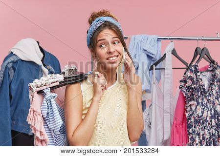 Young Attractive Woman Weaing Scarf On Head And Casual Clothes, Deciding To Refresh Her Wardrobe Doi