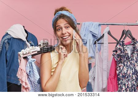Female Model Boasting Her New Purchases, Calling Her Best Friend While Holding Hangers With Clothes