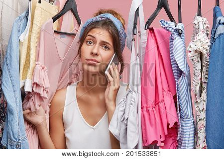 Nothing To Wear Concept. Beautiful Young Woman Dressed Casually Feeling Frustrated Standing Among Mu