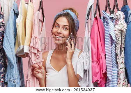 Lovely Female Wearing Scarf On Head And Casual T-shirt, Having Good Mood While Speaking With Someone