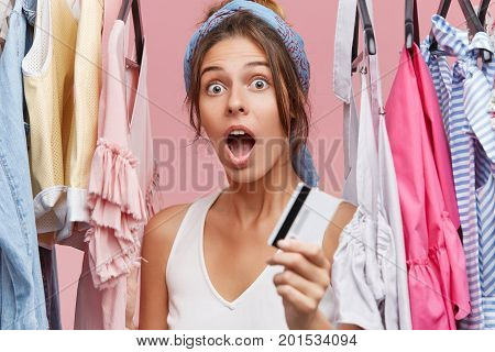 Shocked Female In White T-shirt, Standing Near Sale Clothes Rack, Holding Credit Card, Being Surpris