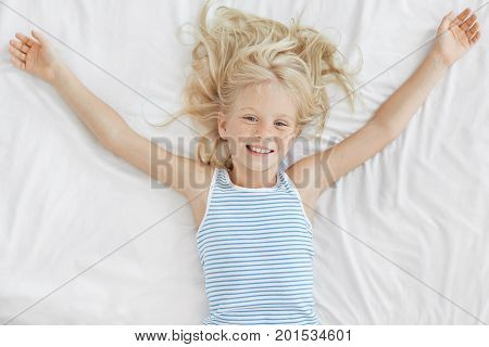 Cheerful Little Girl With Light Hair, Lying In Comfortable Bed On White Bedclothes, Stretching After