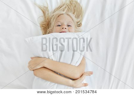 Funny Little Girl With Blonde Hair And Blue Eyes, Having Fun In Bed, Embracing White Pillow, Going T