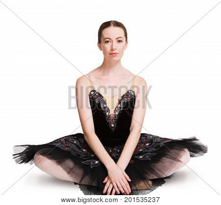 Young graceful ballerina sitting on the floor at white isolated background. Ballet dancer in black costume having rest, posing on camera