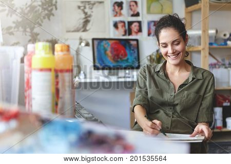 Brunette Cute Female In Casual Clothes, Having Glad Expression, Holding Pencil And Blank Cardboard,