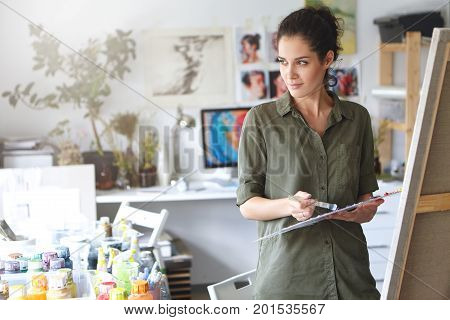 Serious Attractive Female Painter With Dark Hair, Wearing Casual Shirt, Standing In Her Workshop, Ho