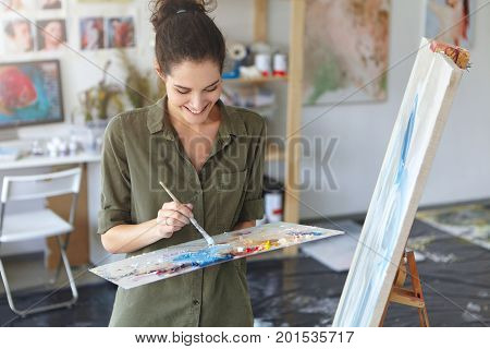 Glad Woman Working As Painter, Standing Near Easel, Holding Paint Brush, Creating Abstract Picture W