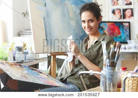 Cheerful Brunette Female Sitting At Workshop, Drawing Colorful Picture On Easel, Using Brightful Oil