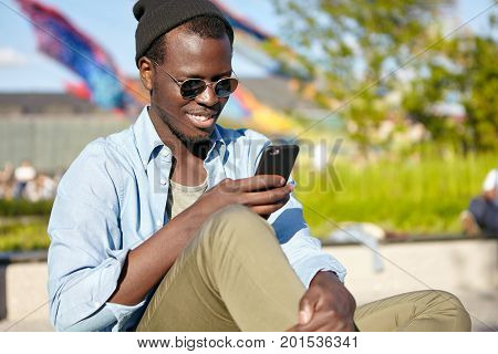 Glad Male With Dark Skin, Wearing Sunglasses And Trendy Clothes, Reading Pleasant Sms On Mobile Phon