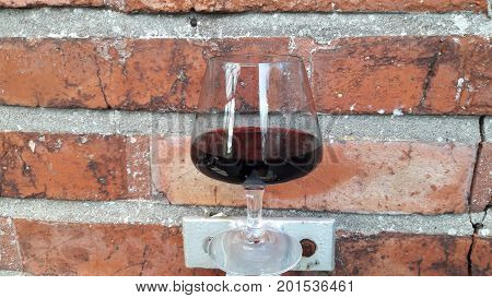 a glass of red wine stand with red brick wall background