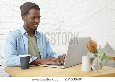 Handsome Afro American Guy Sitting In Cafeteria In Front Of Opened Laptop, Keyboarding And Searching