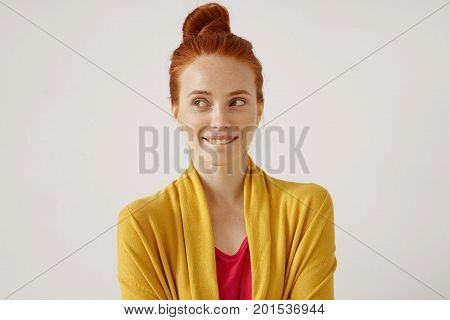 Indoor Portrait Of Mysterious Charming Young European Gimger Female With Hair Knot Looking Sideways