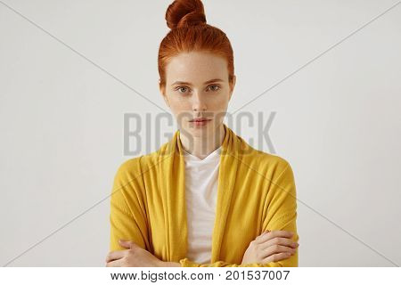 Young Beautiful Freckled Woman With Red Hair Tied In Bun, Wearing Bright Clothes, Keeping Hands Cros