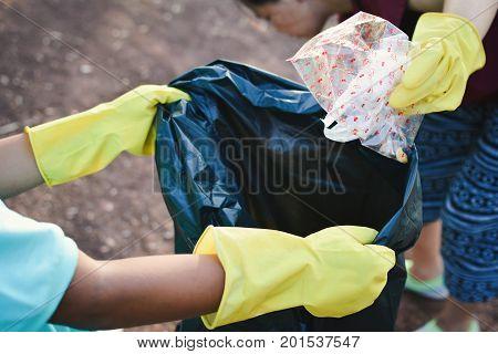 Hands in yellow gloves picking up empty of bottle plastic into bin bag volunteer concept
