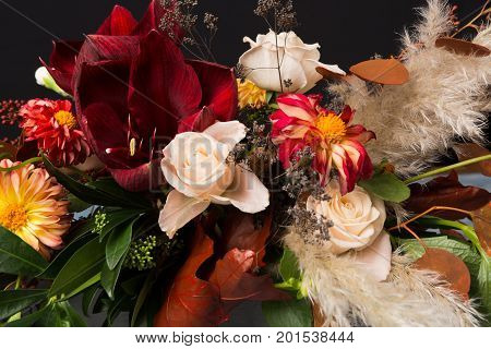Colorful fall bouquet on black background. Autumn composition of roses, tulips, dahlias, dry leaves and herbs closeup. Flower shop and florist design concept