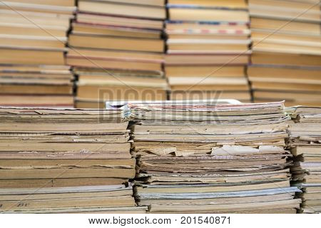 A stack of old school notebooks and a stack of textbooks or books.
