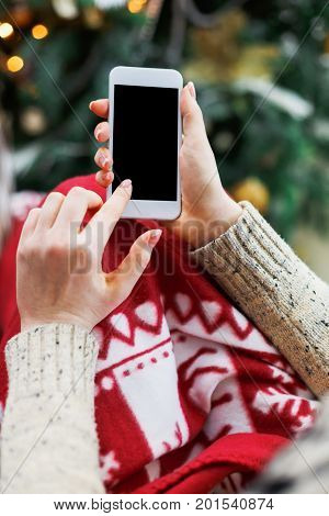 Christmas online shopping. Female buyer makes order at screen of smartphone with copy space. Woman buys presents for xmas eve, sits at home near pine tree with shining lights. Winter holidays sales