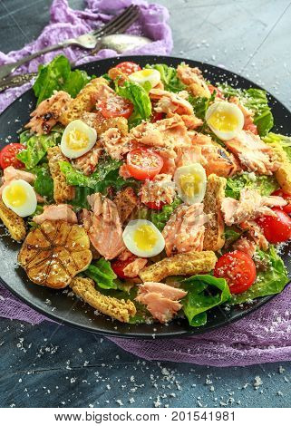 Cesar salad with salmon, cherry tomatoes, garlic, crutons, romaine lettuce and parmesan