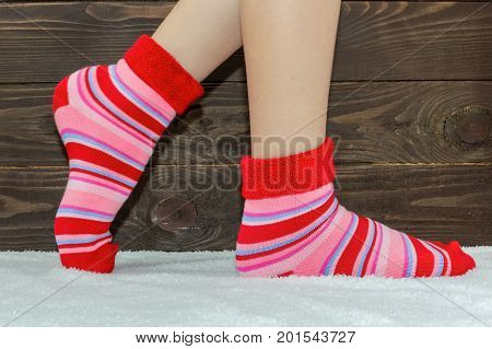 The woman's legs in socks on the rug .Wooden background. Warm stripey socks.