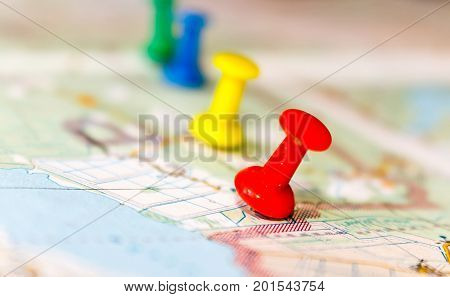 Travel destination points on a map indicated with colorful thumbtacks and shallow depth of field with space for copy.