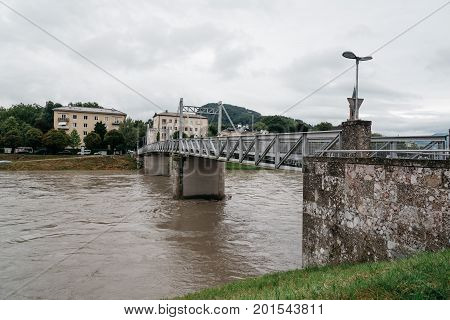 Salzburg Austria - August 6 2017: Steel bridge over the river in Salzburg. The Old Town of Salzburg is internationally renowned for its baroque architecture and was listed as a UNESCO World Heritage Site. Cloudy day of summer