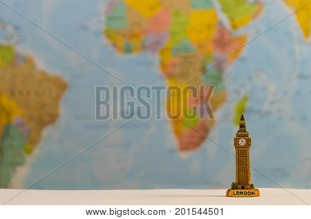 a small model of Big Ben with a world map background