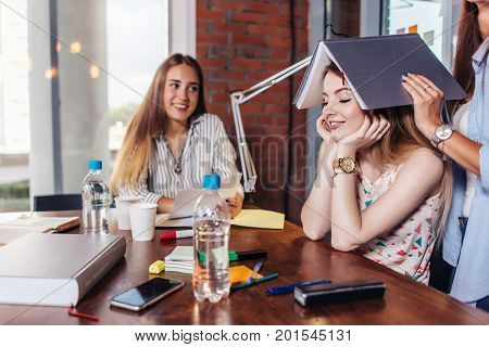 Group of cheerful college students doing homework together and goofing around while sitting at work table in classroom.