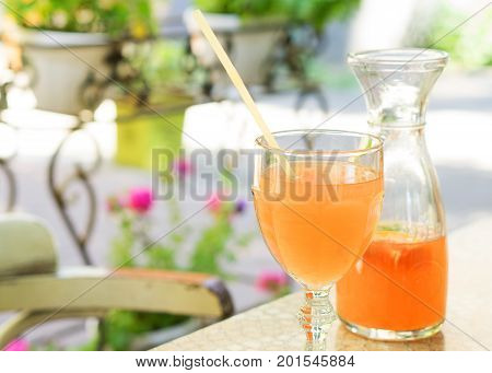 The glass and decanter with a summer grapefruit lemonade, selective focus